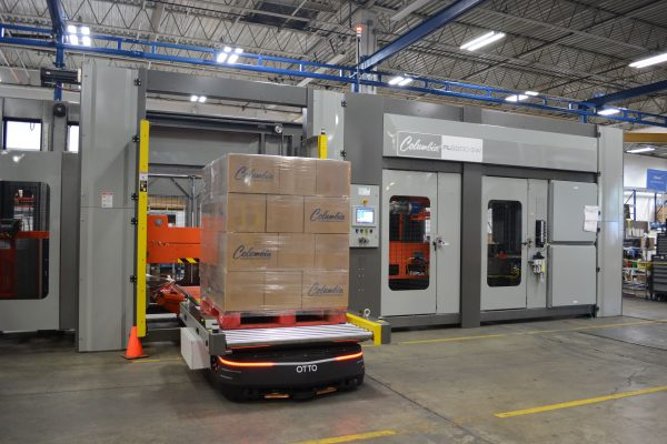 Image of a FL6200SW floor level palletizer with a self-driving OTTO vehicle moving a pallet load.